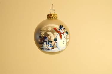 Hvid juletræskugle med snemand og børn på en slæde