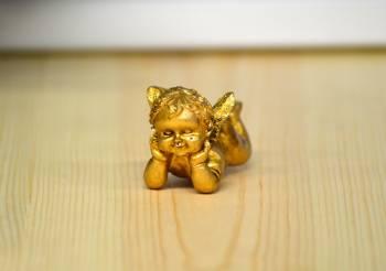 Liggende baby guld engle med hænderne under hovedet